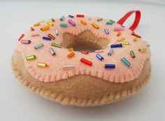 This yummy Orange Cream Donut is hand-sewn covered with vibrant beaded sprinkles on top of a lovely creamsicle orange felt. It will brighten your tree while being child and pet friendly. Each ornament is carefully beaded and hand sewn out of soft Eco Felt that is made from recycled plastic bottles. It adds a touch of whimsy and helps the environment at the same time. The ribbon is sewn inside the top to make it perfect for decorating your tree, gifts, cubical at work, kitchen or anywhere…