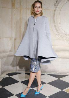 Leelee Sobieski, con un look de Dior en el desfile de éste de París con vestido de jacquard metalizado con abrigo capa con volumen en gris y unos salones en azul cielo como único accesorio.