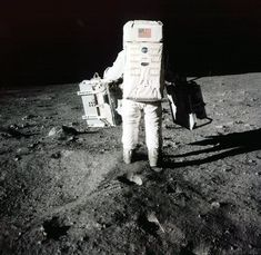 """In this July 20, 1969 file photo provided by NASA, Edwin """"Buzz"""" Aldrin carries scientific experiments to a deployment site south of the lunar module Eagle during the Apollo 11 mission. One experiment involved the inner composition of the moon, and another tried to determine the exact distance from Earth."""