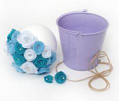 Depois de fazer várias das suas flores de feltro, é só ir perfurando as flores de feltro na bola de isopor. O ideal é que seja uma de 250 mm, mas se o seu balde for um pouco menor do que o normal, você pode usar uma menor, como a de 200 mm. Perfure, preenchendo de flores de feltro, até a metade e depois coloque no balde.