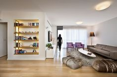 Villa: Built In Bookcase For Book Collection Or Other Stuff Mixed With Grey Fabric Sofa Lounge Also Purple Armchairs Plus Oveal Coffee Table And Stylish Floor Lamp On Varnished Wooden Floor: Exquisite Modern Villas Design