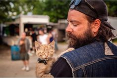 It's absolutely an extraordinary sight to see a heavily-bearded biker carrying a tiny kitten, but Pat Doody and his cute buddy Party Cat are a perfect matc