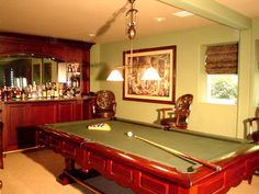 The custom mahogany bar was designed and built specifically to accompany the fantastic pool table. The warm patterned wool carpet and soft olive walls give this room a club-like feeling.