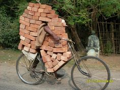 Man escorting a heavy load of bricks with a bicycle