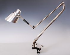 Lamp from 1930s, Czechoslovakia or Germany. Original auction catalog (http://www.e-bijou.com/cohn/cohnauction_katalog2011.pdf , at p. 15) says: aluminum shade, white lacquered parts (puzzling), wooden grips. Full length 130 cm, shade dia. 15 cm.
