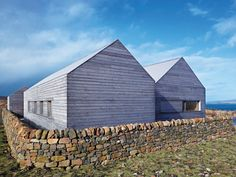 """Borreraig house by Dualchas Architects: At Borreraig, two larch-clad """"sheds"""" slide past each other, surrounded by a dry-stone wall that grips them to the ground. Photo: Andrew Lee"""