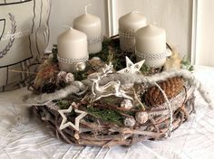Aufwendig gestalteter Adventskranz bestehend aus einem grau gekälkten Rebenkranz und einem darauf sitzenden Mooskranz mit vier hell taupefarbenen Stumpenkerzen, welche mit Strassband umwickelt...