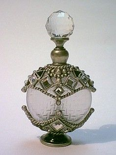 Oval shape frosted bottle with brass and pewter in bronze plated and epoxy treatment with white square pearl stones and rhinestones decor. Cap fits with rod and crystal stone on the top.