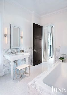 Beautiful bathroom features a Duravit Sink paired with a Jador Faucet situated below a white mirrored medicine cabinet flanked by tubular wall sconces over lower walls clad in carrera marble tile.