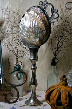 An exquisite iridescent abalone specimen secured in a copula of rustic solder, forever fused to a vintage silver-plate candlestick. Rustic, refined, striking; a lovely addition to your home decor. Vintage elements are kept rustic, and signs of age such as silver patina, bubbled and etched glass are desirable. 14 inches tall.    Welcome to the Trésor Bleu collection of Cross Bottle, Sea Bottle, and Solder Sculpture Art. Created from vintage bottles and unique vessels, candlesticks, natural…