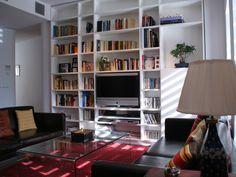 Librería realizada en mdf lacado blanco integrando el televisor y una zona cerrada para almacenaje de vajilla y otros objetos. Diaco fabrica todo tipo de muebles para salón totalmente a medida y diseño personalizado, con materiales muy variados, como acero inox, madera, lacados, sintéticos, vidrios, etc.