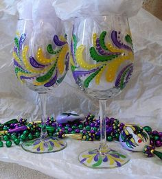 Celebrate Mardi Gras in style with this pair of festive, hand painted wine glasses. Each glass is individually painted without a pattern with purple , green and gold swirls. Each is individual and unique. Great gift idea! Contact me if you would like more, or if you would like a similar design in different colors. 12 oz. if filled to the brim and 7 1/2 tall. Hand wash recommended.