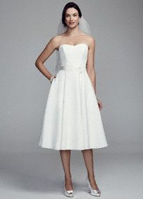 Short, flirty and sweet, you will look lovely in this wedding dress! Strapless faille bodice with ultra-feminine sweetheart neckline features a floral sash at natural waist. No Train. Sizes 0-14. Fully lined. Back zip. Imported polyester. Dry clean only.This neckline is shaped like the top of a heart and is flattering to the decolletage.Falls at your natural waistline.A popular neckline for brides seeking a stylish and versatile look (offering unlimited jewelry and accessory options).A…