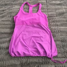 GAPfit workout tank GAPfit workout tank in lovely shade of pink. Racer back design with loose fitting bottom and tie at hem. Excellent condition, only worn a few times (Love this top, but Sadly my chest is so damn small I can't fill out the top of it!) GAP Tops Tank Tops