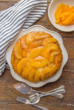 peach upside down cake on a plate with sliced peaches in a small bowl