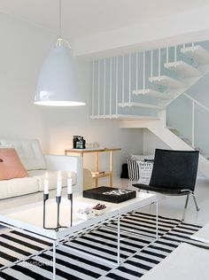 Living room with white tray tables by Hay and Caravaggio pendant by Lightyears. Via Less Is More.