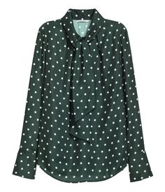 Dark green/dotted. Loose-fitting satin blouse. V-neck with tie, long sleeves, cuffs with buttons, and gently rounded hem.