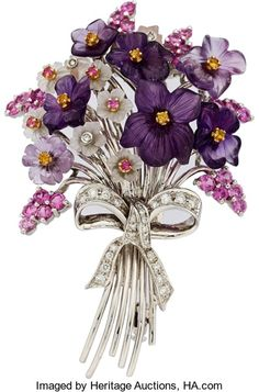 Multi-Stone, Diamond, White Gold Brooch, SANTAGOSTINO. The brooch features full-cut Diamonds (approx. 0.30 carat), enhanced by round-cut pink Sapphires (approx.2.75 carats), further enhanced by carved AMETHYST measuring 8.80 x 8.50 mm to 15.15x12.45 mm, accented by carved Quartz measuring 5.35 x 5.35 mm to 6.60 x 6.35 mm, complemented by round-cut yellow Sapphires (approx. 0.25 carat), set in 18k white Gold, marked Santagostino.   Estimate: $2,500 - $3,500.