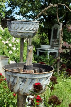 Love! Old bundt pans mounted on sticks to use as planters