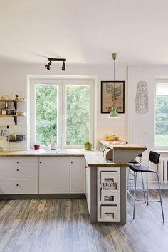 Nadstawka nad blatem roboczym tworzy ciekawy wizualnie i praktyczny barek w tym aneksie kuchennym. Dodatkowo maskuje on widok kuchni z perspektywy salonu. Barek i strefa robocza są oświetlone przez dwa oddzielne źródła światła.