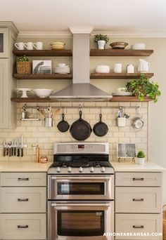 I like the hanging cast iron pots on the wall Little Rock Arkansas Home Makeover by Kathryn LeMasters | range hood incorporated into shelving wall