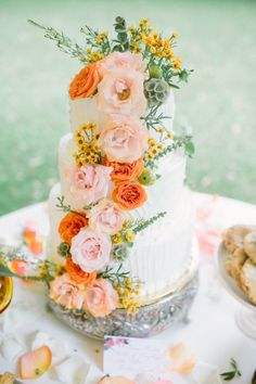 This three-tier buttercream frosted cake is accentuated with various wild yellow and green flowers that add height. Pink and coral-colored flowers line down the center of the design to create a beautiful focal-point to tie all the wedding colors back together.