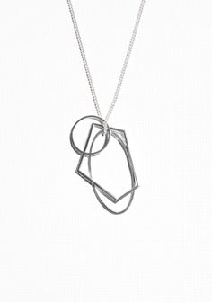 Geometrically shaped pendants suspended on a thin silver-tone chain make this necklace a sophisticated accessory.