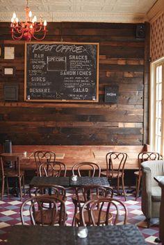 Esse parece o bar visto da entrada! Interessante a ideia do quadro, assim poderiamos espalhar mais de um menu pelo bar. Piso também é legal.  A ideia de usar cadeiras de madeira e poltronas deixa o ambiente mais aconchegante.
