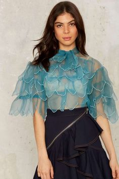 This semi-sheer vintage blouse comes in blue and features a high neck with tie, wide sleeves, and tiered ruffles throughout.