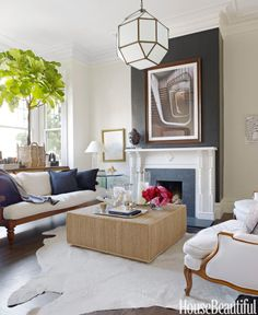 Antique meets modern in the living room of a San Francisco Victorian. Designer Ken Fulk chose a black and white palette, softened with neutrals and natural textures. The chimney breast is papered with Ralph Lauren's black Yacare Crocodile, and a Ralph Lauren Peyton ottoman sits on a cowhide rug from Frank's Leather & Hides.