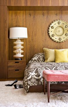 Inside a Midcentury Home with a Feminine Touch // Feminine bedroom design with pink bench, oversized lamps, and ikat bedcover