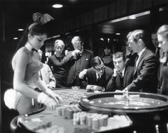 """A croupier Bunny makes bets for distressed-looking """"punters,"""" London, 1967"""