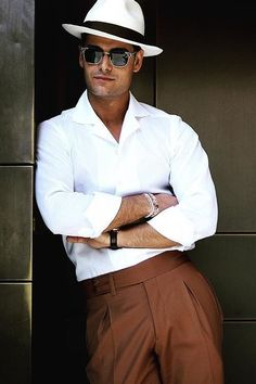 55b6e2ef581 Summer fashion inspiration with a white fedora sunglasses white button up  shirt with rolled up sleeves wrist accessories brown pleated pants