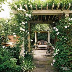 A small yard can benefit from the added height of a pergola-or more. Here, matching pergolas spaced a couple yards apart are framed with lush greenery; slate pavers that stretch under create a seamless look.