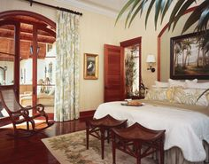 Adorned with banana leaves and birds of paradise, Brunschwig & Fils' cotton/linen fabric fashions the draperies and shams in this master suite.