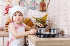 Kleines Mädchen in der Schürze und Mütze des Kochs steht in der Küche in der Nähe von Herd im Haus. Helfer der Mutter. 2 Jahre alt.