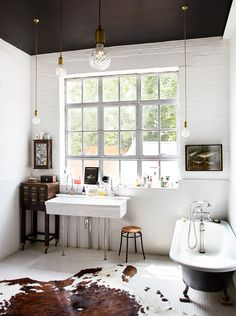 black and white bathroom with white brick, square tiles, crystal pendants, a cowhide rug, and a clawfoot tub