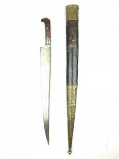 A Large Khyber Knife, T-section blade, two-piece riveted and ribbed horn grips, contained in a leather wrapped wooden scabbard with foliate embossed brass mounts. Indian Sword, Blacksmith Forge, Arm Armor, Masons, Fantasy Rpg, Knives And Swords, Islamic Art, Knights, Horns