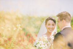 Bride & Groom summer wedding portrait, through grasses. Wold Top Brewery, Hunmanby, Scarborough, North Yorkshire.