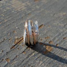 sterling silver spinner ring- 3 bands, 2 gold, 1 hammered sterling. $74.00, via Etsy.