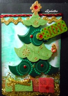 ATC-Oh Christmas Tree Artist Trading Card - One of a Kind. Parchment paper background, inked in green, 3-D tree and presents, JOY sticker. jewels, red rope, gold bric brac, gold glitter.