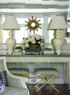 Mirrored walls, and pale pale blue paneling, and perfect glimmers of brass in this beautiful living room vignette in a home in Greenwich, Connecticut by Ashley Whittaker.