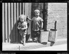 Two children standing on footpath during the Great Depression, Surry Hills, Sydney, 20 June 1932