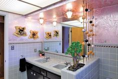 """The bathroom of this 1955 traditional ranch house in Tulsa, Okla., has a planter in the tile half-wall and a planetary room divider. (Gringeri-Brown notes in """"Atomic Ranch Midcentury Interiors"""" that the 1970s foil wallpaper """"will probably be coming down."""")"""