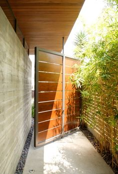 KAA - unbelievably cool door/gate Lausell can create this pivot entrance gate, only limited by your imagination. Panels could be relatively maintenance free fixed aluminum louvers in place of wood.