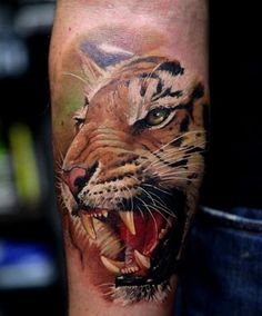 What does tiger tattoo mean? We have tiger tattoo ideas, designs, symbolism and we explain the meaning behind the tattoo. Realistic Tiger Tattoo, Tiger Tattoo Images, Tiger Tattoo Meaning, Tiger Head Tattoo, Head Tattoos, Body Art Tattoos, Sleeve Tattoos, Cool Tattoos, Music Tattoos