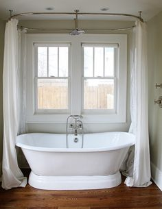 love those curtains. how fun would it be to soak in this thing?  (amy alday via Flickr)