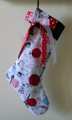 "This non traditional Christmas Stocking was made for all those who love  Paris. The fabric is 100% cotton and and is called Paris Cafe. The band,  lining and loop and made from 100% black cotton. To complete the look I  created a bow out of red and white polka dot grosgrain ribbon and white  organdy ribbon.  The finished stocking measures 17"" from the top to the longest point at the  toe and is 7"" wide. The red band is 3"" wide.  This stocking will be an added tradition for years to come!"