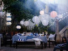 Ein gedeckter Tisch in Blau und Weiß, u. a. hängen darüber SOLVINDEN LED-Solarhängeleuchten in unterschiedlichen Ausführungen