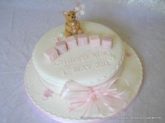 Elegant white round christening cake decorated with some simple pink and white flowers. Topped with a handmade sugar modelled teddy bear and the building blocks spelling the childs name. Tied together with a delicate chiffon ribbon